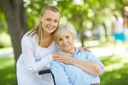 Pretty nurse and senior patient looking at camera outside